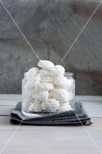 A jar of meringues with hazelnuts and icing sugar