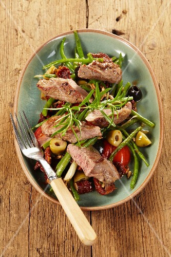 Lamb fillet with green beans, olives and tomatoes