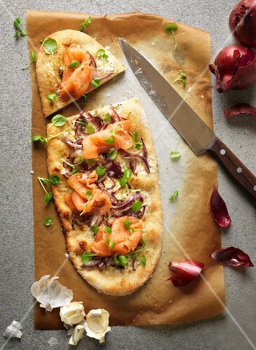 Pizza baked with sour cream and garlic, topped with smoked salmon, red onions and watercress
