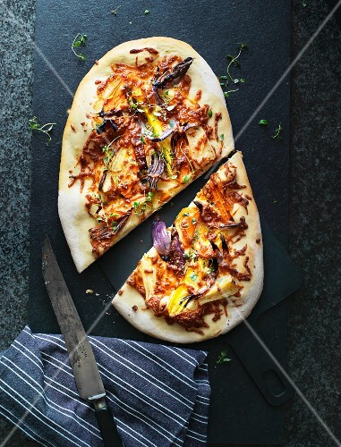 Pizza with red onions, colourful carrots and yellow pepper