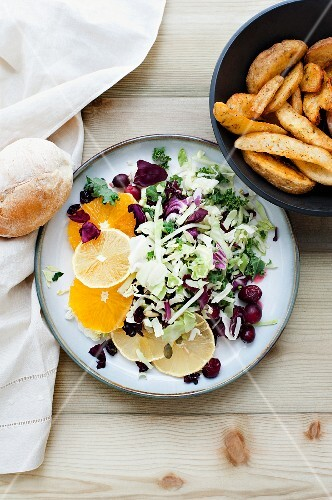 A mixed leaf salad with citrus fruits, cranberries and a side of chips