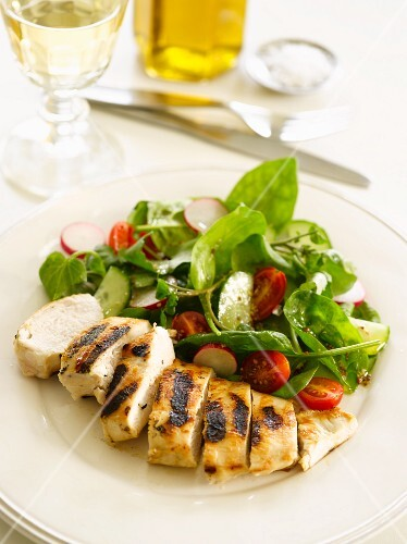 Grilled chicken breast with a spinach, radish and tomato salad