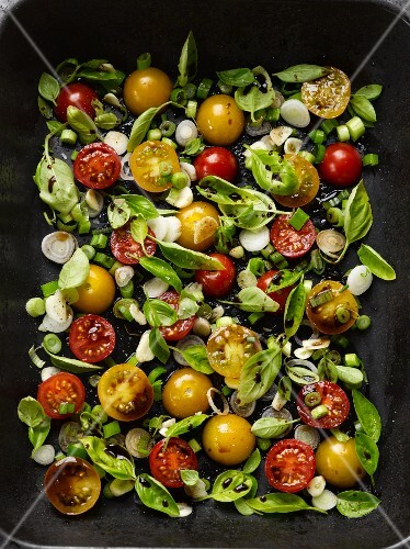 A bed of vegetables: cherry tomaotes, garlic, onions and basil (raw)
