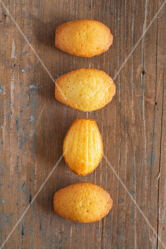 Four madeleines on a wooden surface
