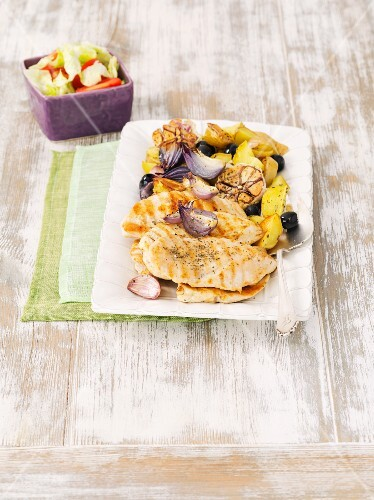 Grilled chicken breast with roast potatoes, garlic and red onions
