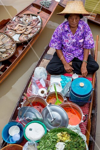 A woman sitting in a floating market; Thailand