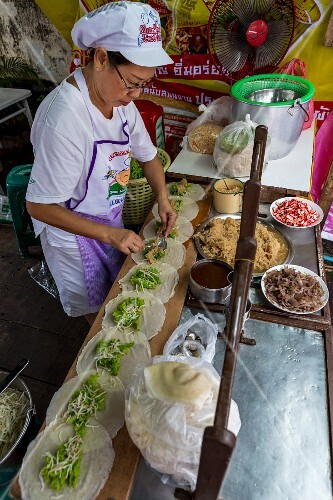 A woman preparing spring onions in a cookshop in Phuket, Thailand