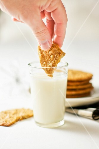 A biscuit being dipped into a glass of milk