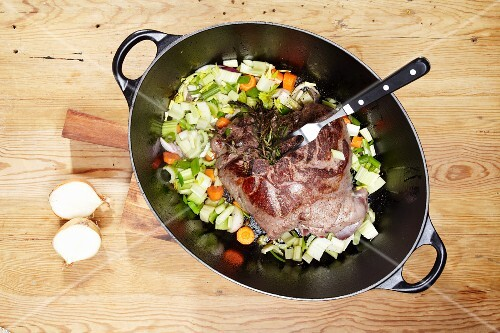 Leg of venison with rosemary, onions, leeks and carrots in a braising dish