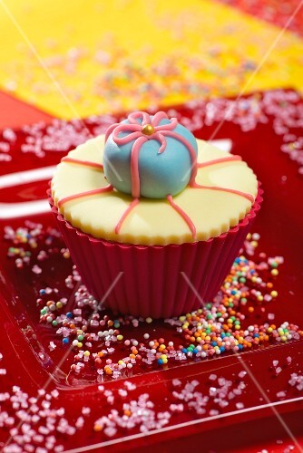 A decorated cupcake on a red plate with sprinkles