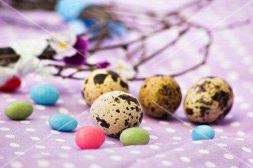 Quail's eggs and sugar eggs on a spotted cloth