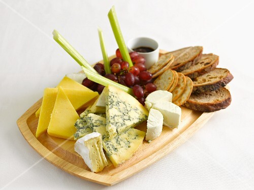 A cheese platter with bread, grapes and celery