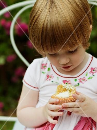 A little girl holding an elderflower cupcake