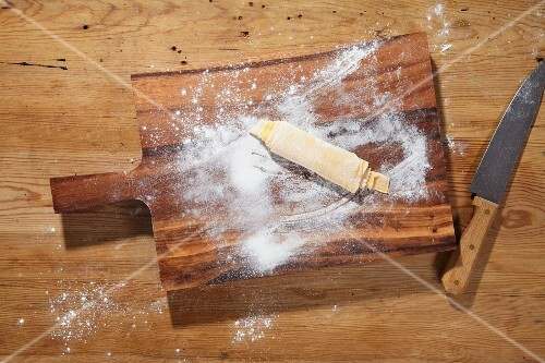 Rolled-up pasta dough on a chopping board