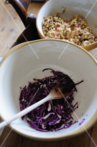 Sliced red cabbage in a bowl with a wooden spoon