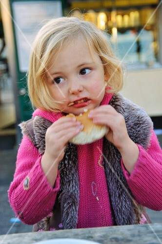 A little girl eating a bread roll at a market