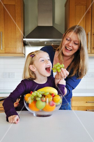 A mother feeding her daughter grapes in the kitchen