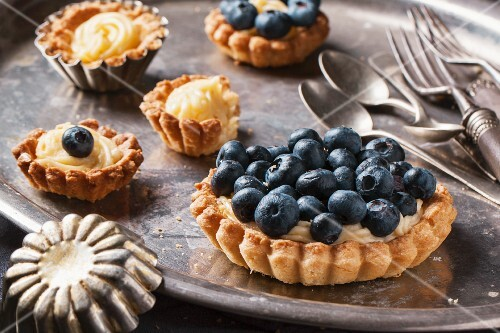 Silver cutlery and various different sized blueberry tarts with lemon cream, one with a bite taken out