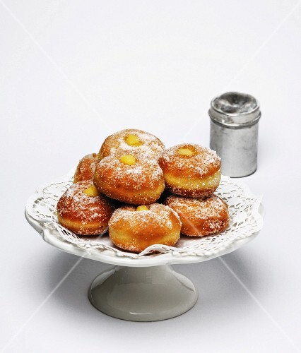 Doughnuts filled with vanilla cream and dusted with icing sugar