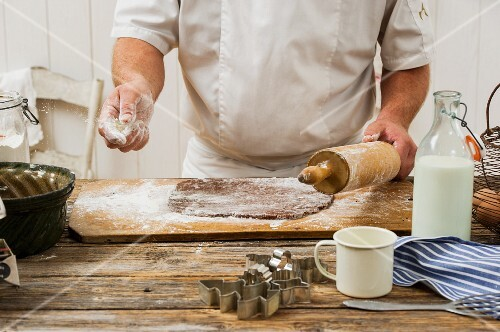 A confectioner sprinkling flour onto biscuit dough