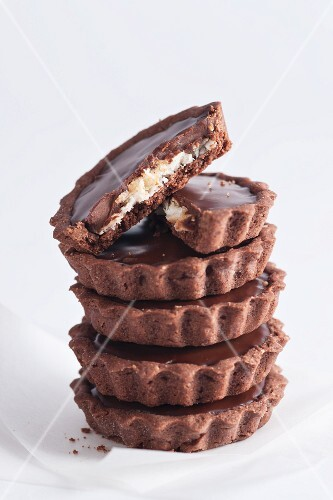 A stack of chocolate tartlets with a coconut filling