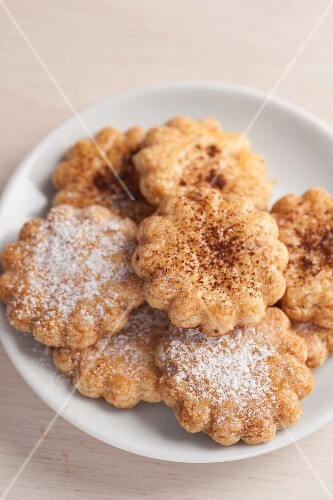 Flower-shaped biscuits with icing sugar and cocoa powder