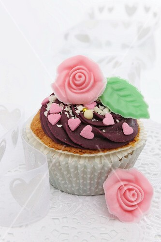 A cupcake decorated with chocolate cream and a marzipan rose for Valentine's Day