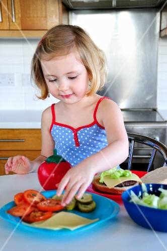 A little girl topping a hamburger with tomato