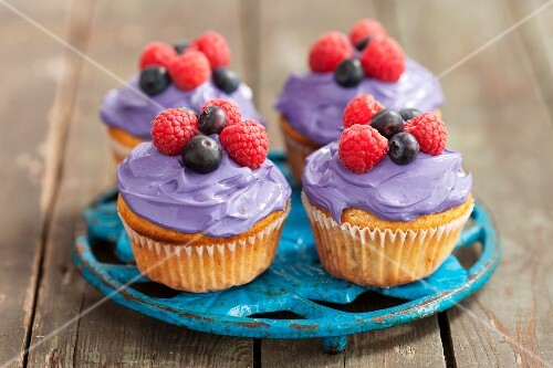Cupcakes decorated with berry cream and fresh berries on a saucer