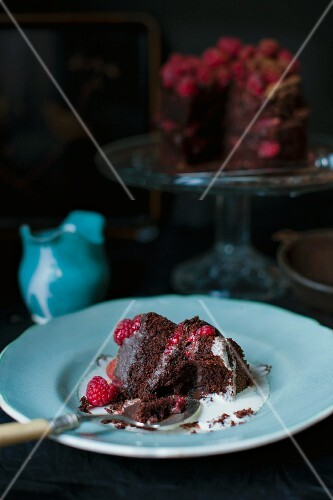 A slice of dark chocolate and raspberry cake with a bite taken out