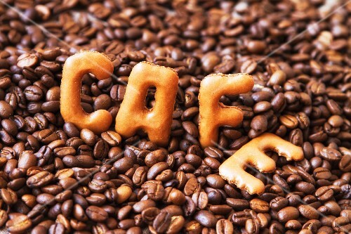 The word 'cafe' written using alphabet biscuits on top of coffee beans