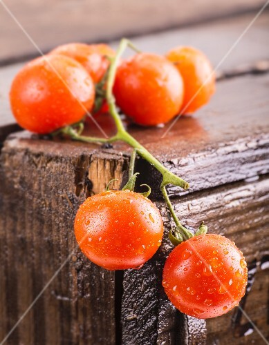 Freshly washed vine tomatoes on a wooden crate