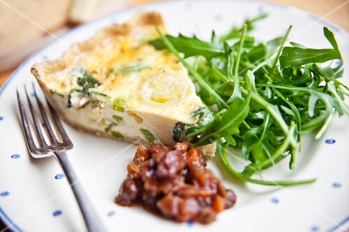 A slice of cheddar and leek quiche with rocket and apple chutney