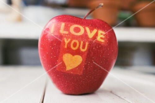 A red apple carved with the words I LOVE YOU and a heart