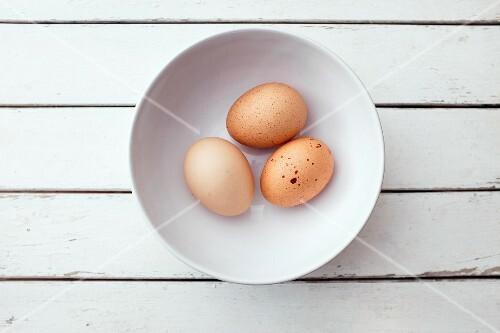 Three organic eggs in a bowl