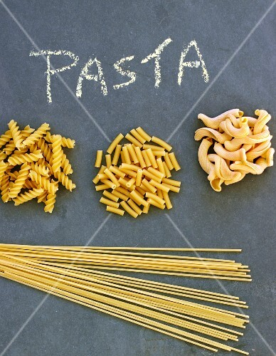 Various different types of pasta on a slate sheet