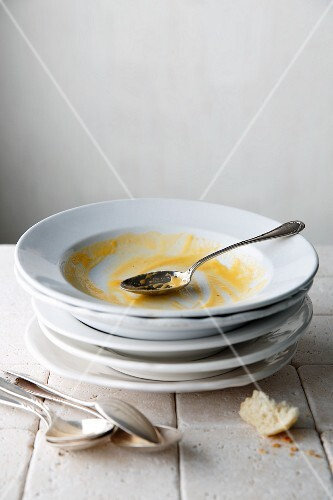 A stack of used soup bowls with spoons