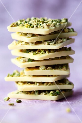 A stack of white chocolate with pistachios on a purple surface