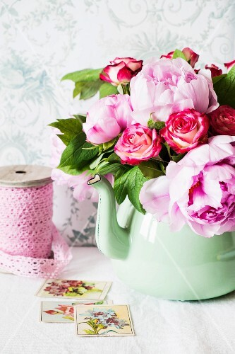 A bunch of peonies and roses in an old-fashioned green metal jug on a shelf in front of a wallpapered wall