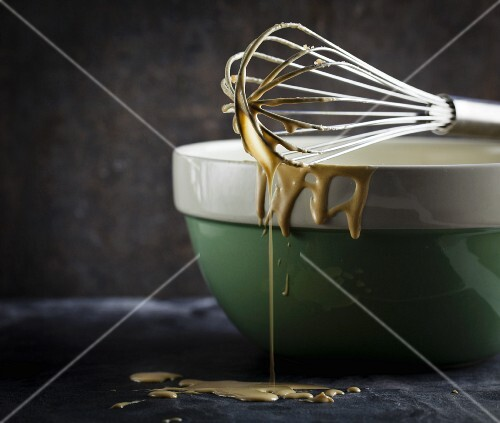 Cake mixture dripping off a whisk balanced over a ceramic bowl