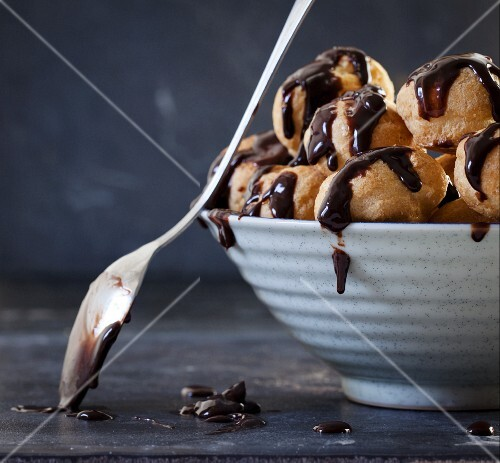 A bowl of profiteroles with chocolate sauce and a spoon