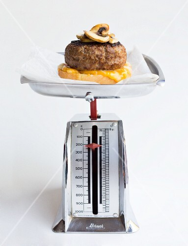 Cheese burger with mushrooms on a pair of mechancial scales