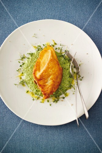 Baked salmon fillet with a horseradish coating on a bed of herb cream