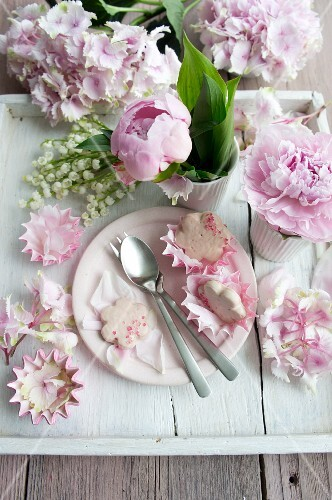 Rose-petal biscuits, peonies, lily-of-the-valley and hydrangea flowers on white wooden tablet