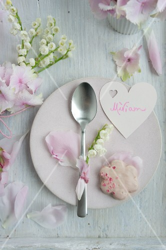 Heart-shaped name tag, rose-petal biscuits and spoon decorated with lily-of-the-valley on plate