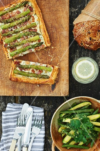 Asparagus cake, courgette and bean salad, a loaf of bread and lemon water on a picnic table