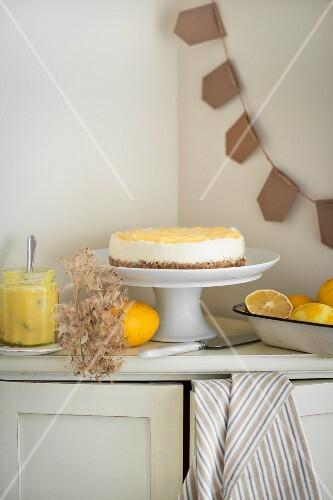Lemon cheesecake with a bowl of fresh lemons and a jar of lemon cream next to it