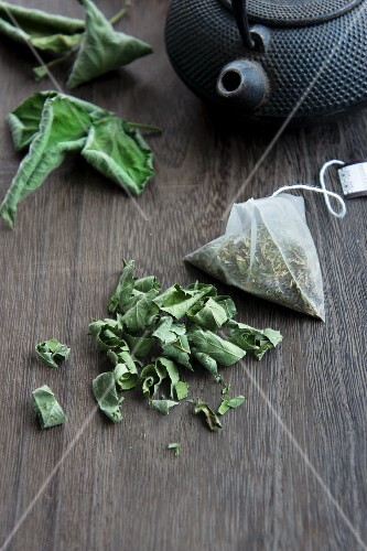 Dried blackberry leaves, lose and in a teabag with a teapot next to them