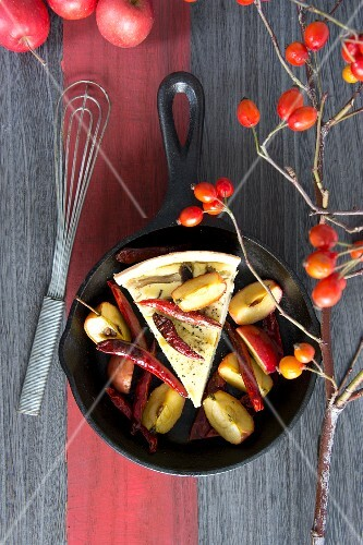 A slice of mushroom quiche with apples and dried chilli peppers