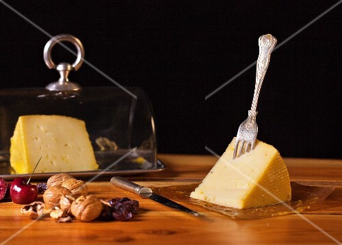An arrangement of cheese with cherries and walnuts